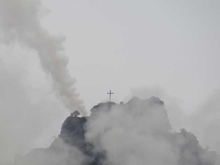 Cross on a mountain top hardy visible from the exhaust produced by factories from the Alaverdi Industrial complex