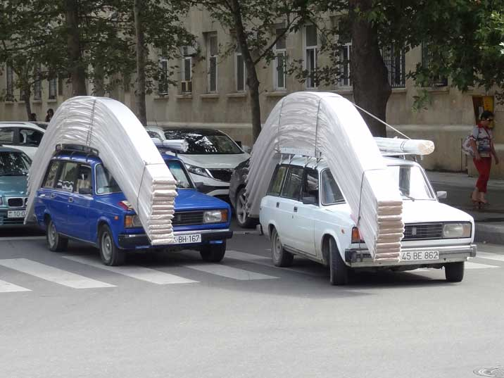 Two VAZ 21043 station wagons transporting a load of building materials on the roofs of the cars in the Azeri capital Baku