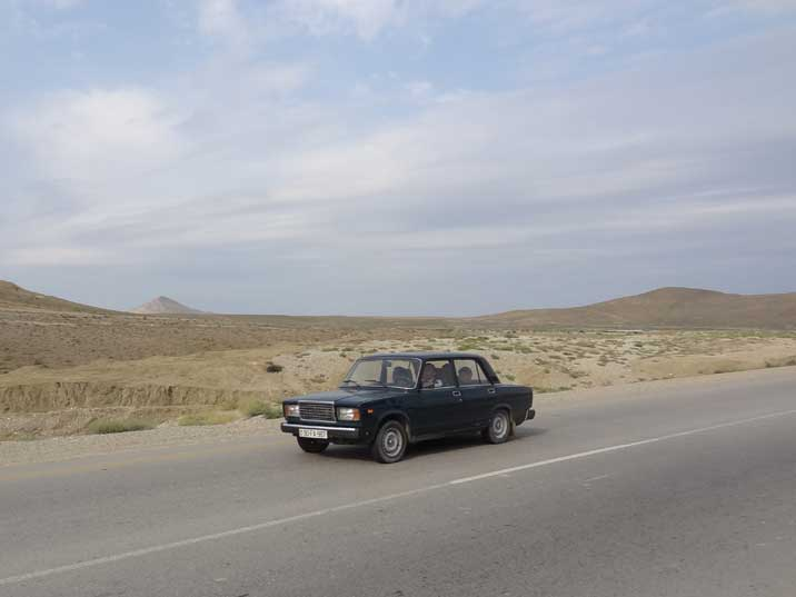 Azeri family passing the dry dessert like landscape of Gobustan in their Lada