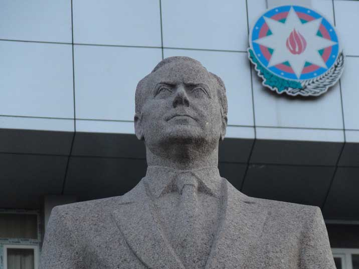 A statue of Heydar Aliyev the referred Azeri President with the Azerbaijan coat of Arms in the background