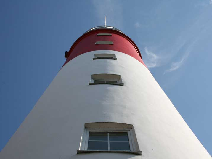 The red and white Baltiysk lighthouse with the blue Baltic sky