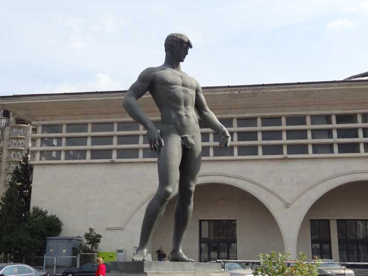 Soviet statue of a naked athlete only dressed with a fig leave in front of the impressive Tbilisi Sport Palace