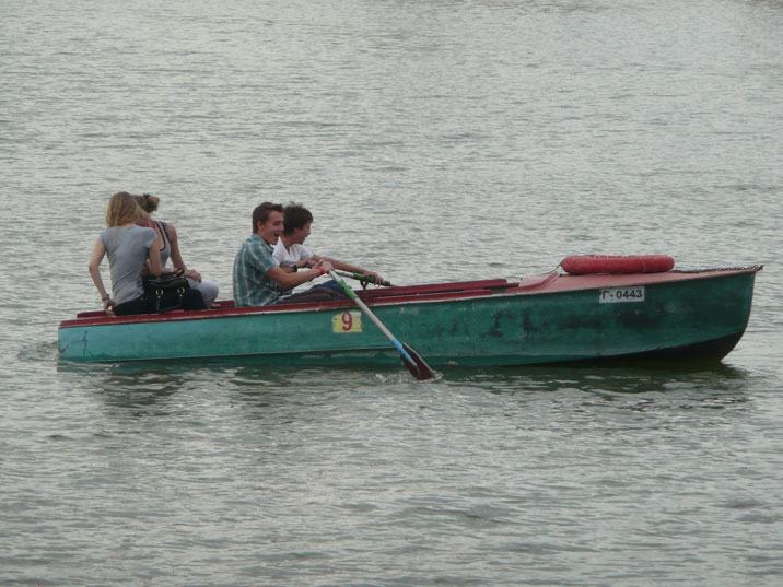 Rowing kids in a rented boat on the lake that is part of central park in Karaganda