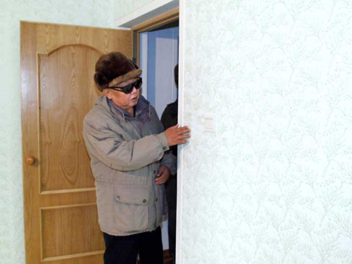 Kim Jong Il looking at a wall in factory somewhere in North Korea