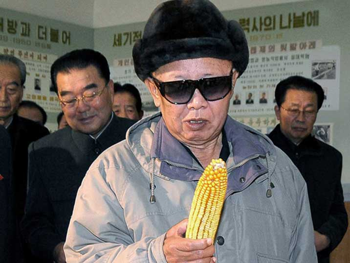 Kim Jong Il looking at a piece of corn in front of bystanders
