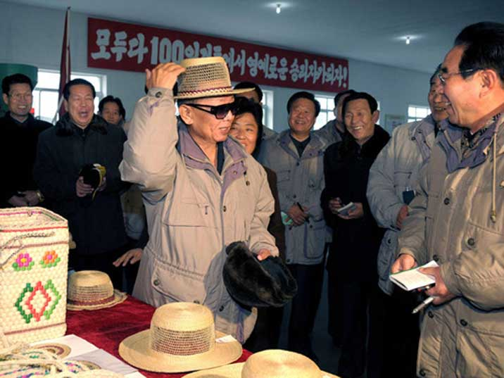 Kim Jong Il amusing his entourage by trying on a straw hat