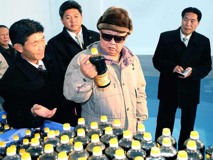 Kim Jong Il looking at a bottle of soy presented in a factory