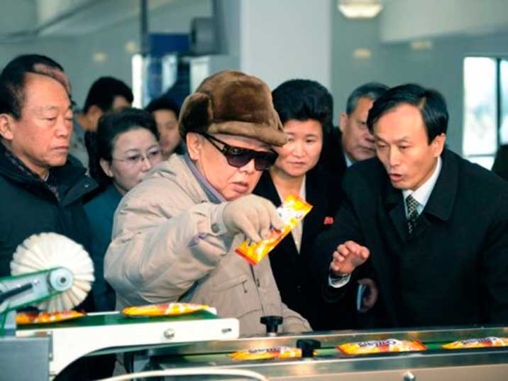 Kim Jong Il looking at candy bar while being briefed by a manager