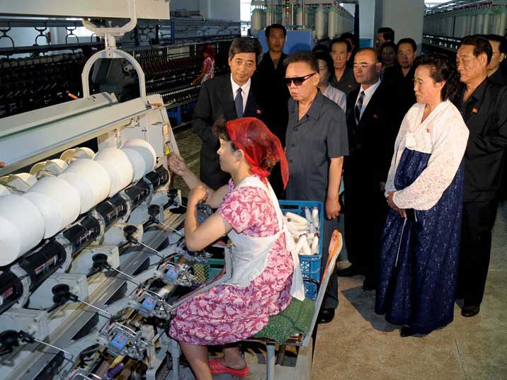 Kim Jong Il watching a woman in a textile mill in Pyongyang