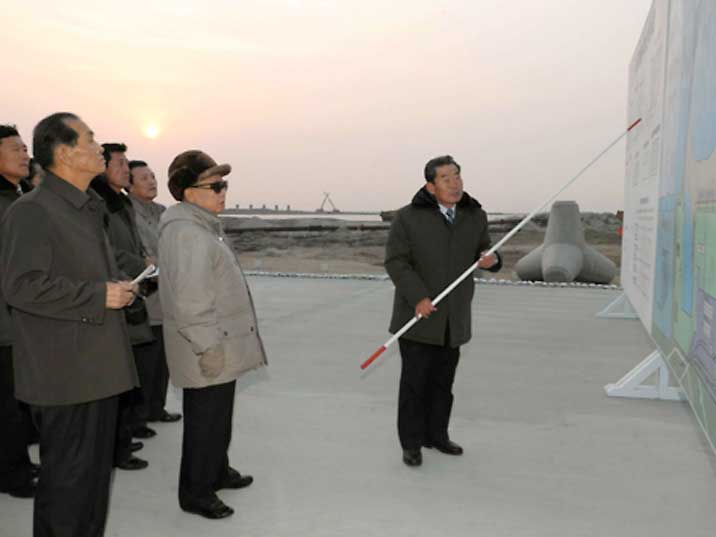 Kim looking a giant map in a harbour facility in North Korea