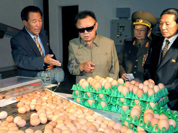 A farm executive explains Kim Jong Il how eggs are packaged