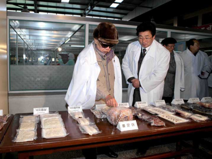 Kim Jong Il looks at various types of meat sealed in plastic