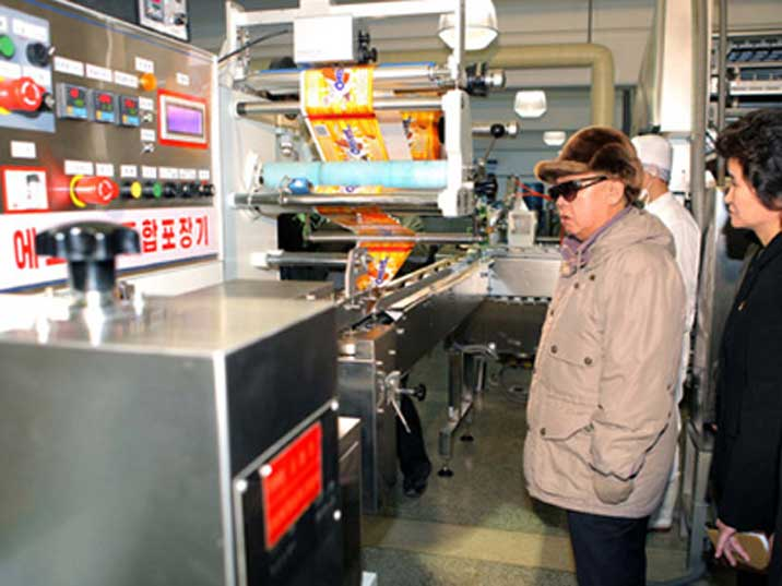 Kim Jong Il seems to be intrigued by a packaging machine