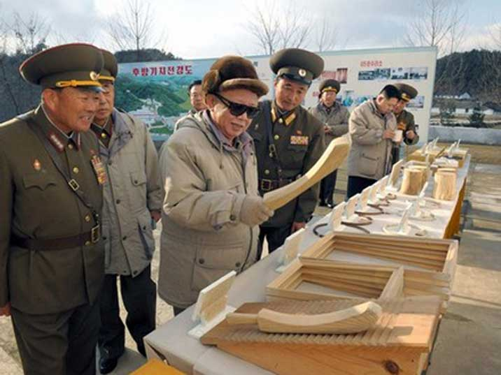 Kim Jong Il is amused by a piece of wood displayed outdoors