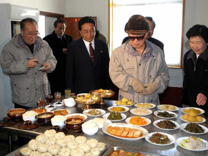 Kim Jong Il looking interested at various dished in a restaurant