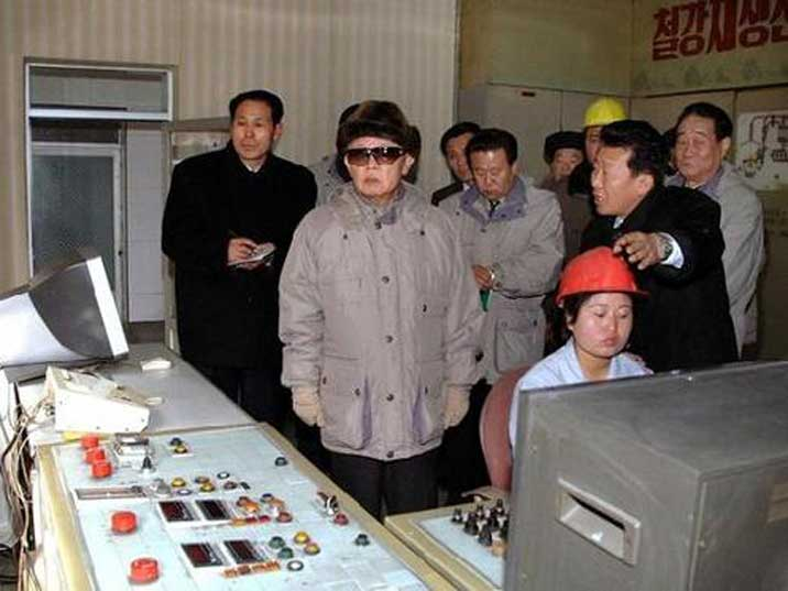Kim Jong Il looking at machine operating equipment in a factory