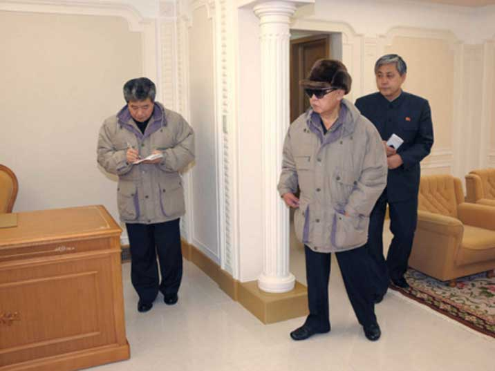 Kim Jong Il looking at a desk in a Pyongyang production facility
