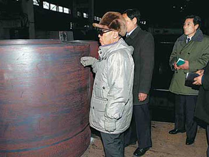 Kim Jong Il looking at a roll of steel in a steel factory