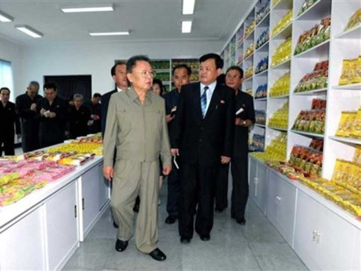 Kim Jong Il looking at neatly displayed crisps in a store