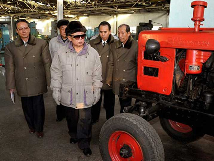 Kim Jong Il looking at tractor displayed in a production facility
