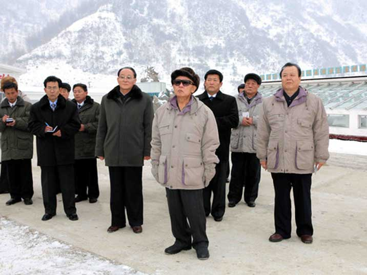 Kim Jong Il looking up on an army base in a snowy landscape