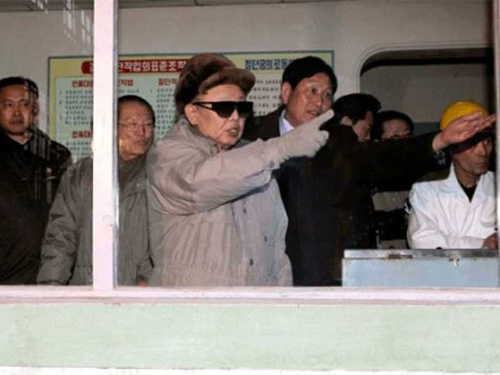 Kim Jong Il pointing at something in a North Korean factory