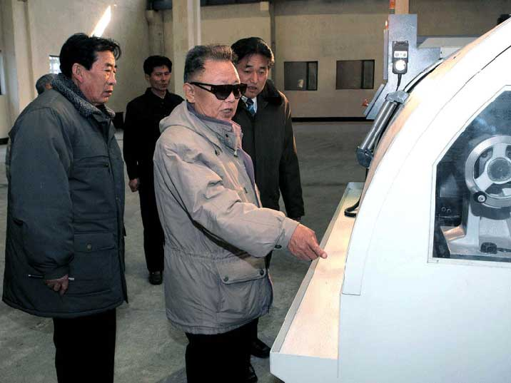 Kim Jong Il providing field guidance on how to operate a machine
