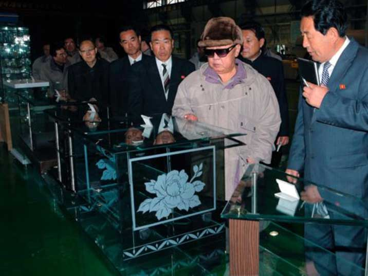 Kim Jong Il looking at glass furniture in a production facility