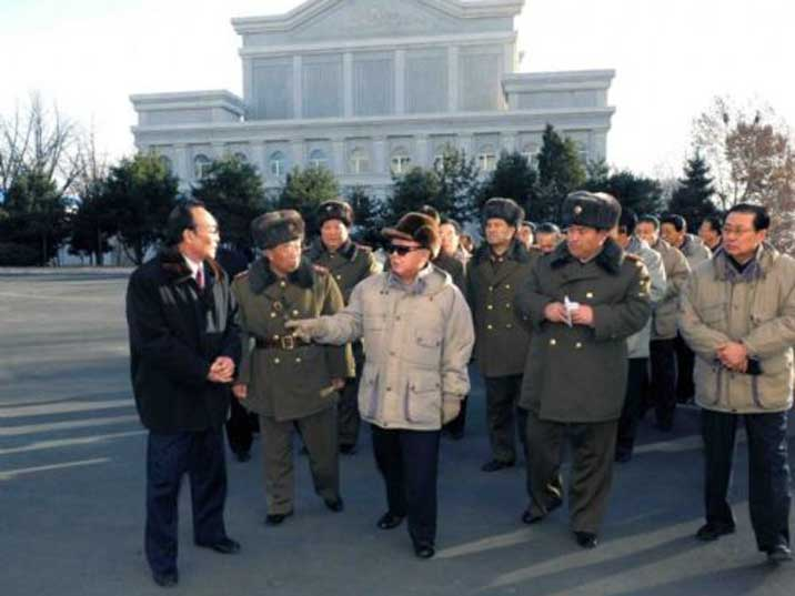 Kim Jong Il surrounded by army looking to a subordinate