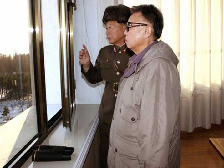 Kim Jong Il looking at a KPA facility from a window with a general