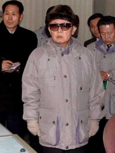 Kim Jong Il looking at something while his followers take notes