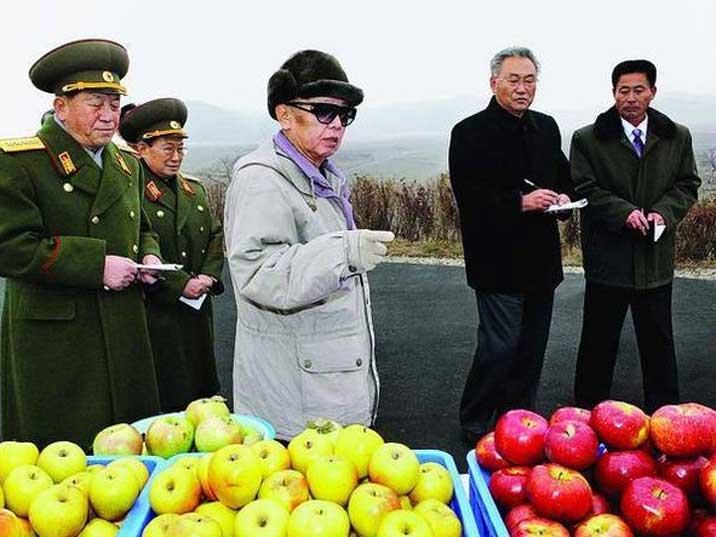 Kim Jong Il looking at apples on a farm of the Korean Army