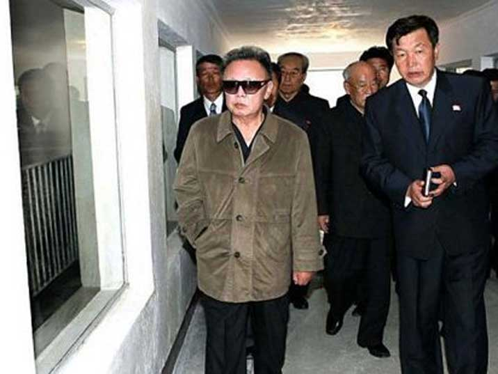 Kim Jong Il looking at a window while inspecting a facility