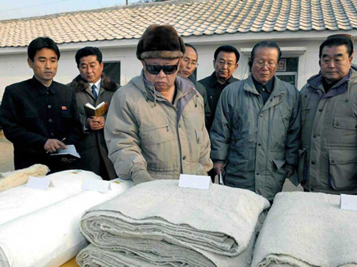 Kim Jong Il looking a cloth produced in a North Korean factory