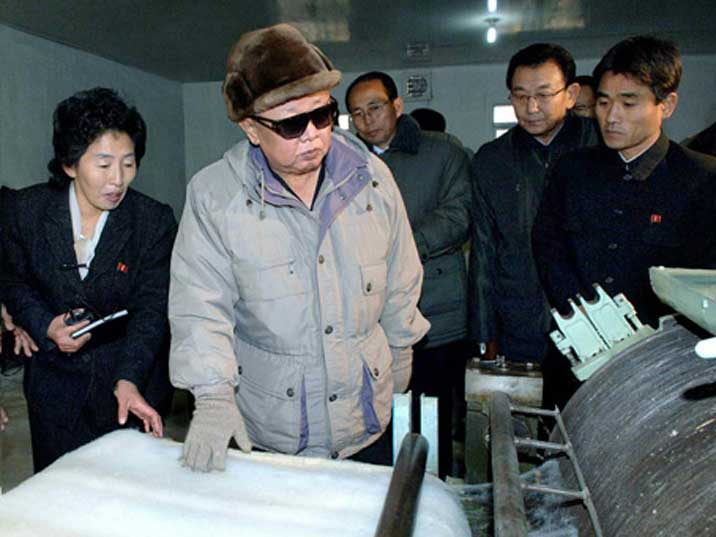 Kim Jong Il looking at a weaving machine in a Pyongyang factory