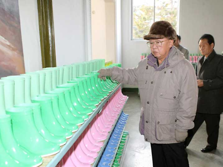 Kim Jong Il looking at children's boots in various colours