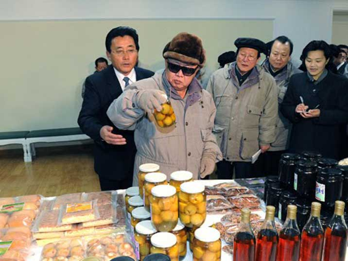 Kim Jong Il looking very interested at a jar with little apples