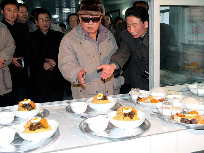 Kim Jong Il looks at the lunch with a large crowd around him