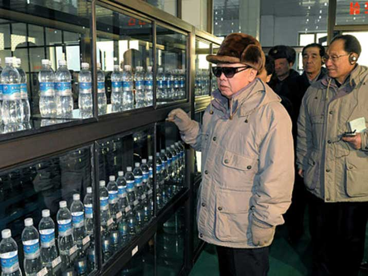Kim Jong Il looking at water bottles displayed in glass cases