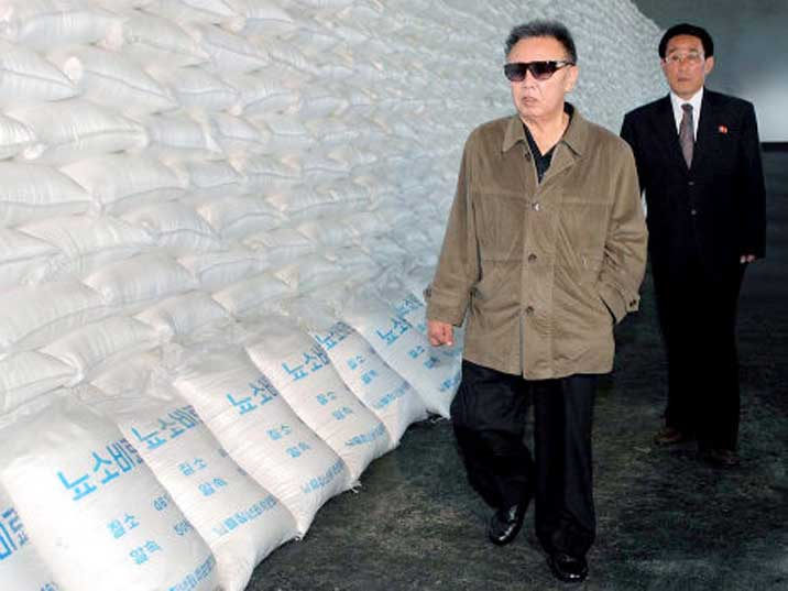 Kim Jong Il looking at a pile of bags filled with raw materials