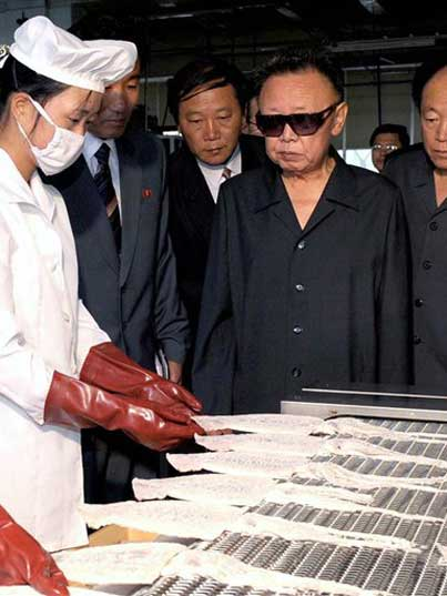 Kim Jong Il looking at fish processed in a Pyongyang factory