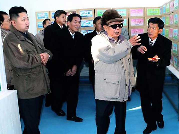 Kim Jong Il looking at boxes filled with an unknown content