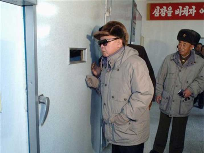 Kim Jong Il looking trough a peak whole in a steel door