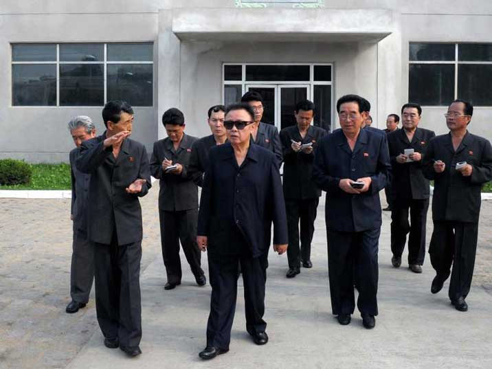 Kim Jong Il looking at the size of something in a production plant