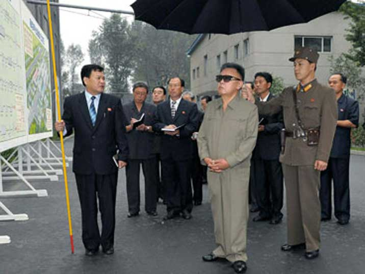 Kim Jong Il looking at a presentation with a big map outdoors