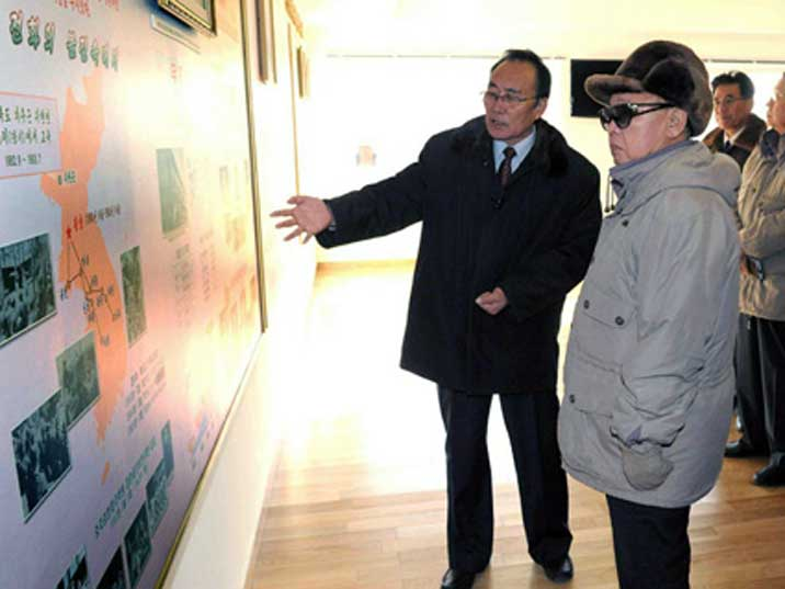 Kim Jong Il looking at a Korean map with some kind of network