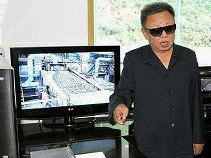 Kim Jong Illooking at a computer with a video of a factory