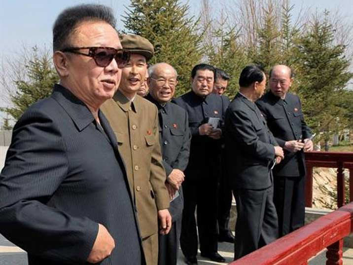 Kim Jong Il looking at a something surrounded by loyal followers