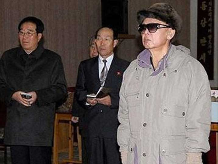 Kim Jong Il looking at something in a theatre or other building
