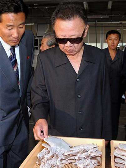 Kim Jong Il looking at dried meat in a Pyongyang food facility